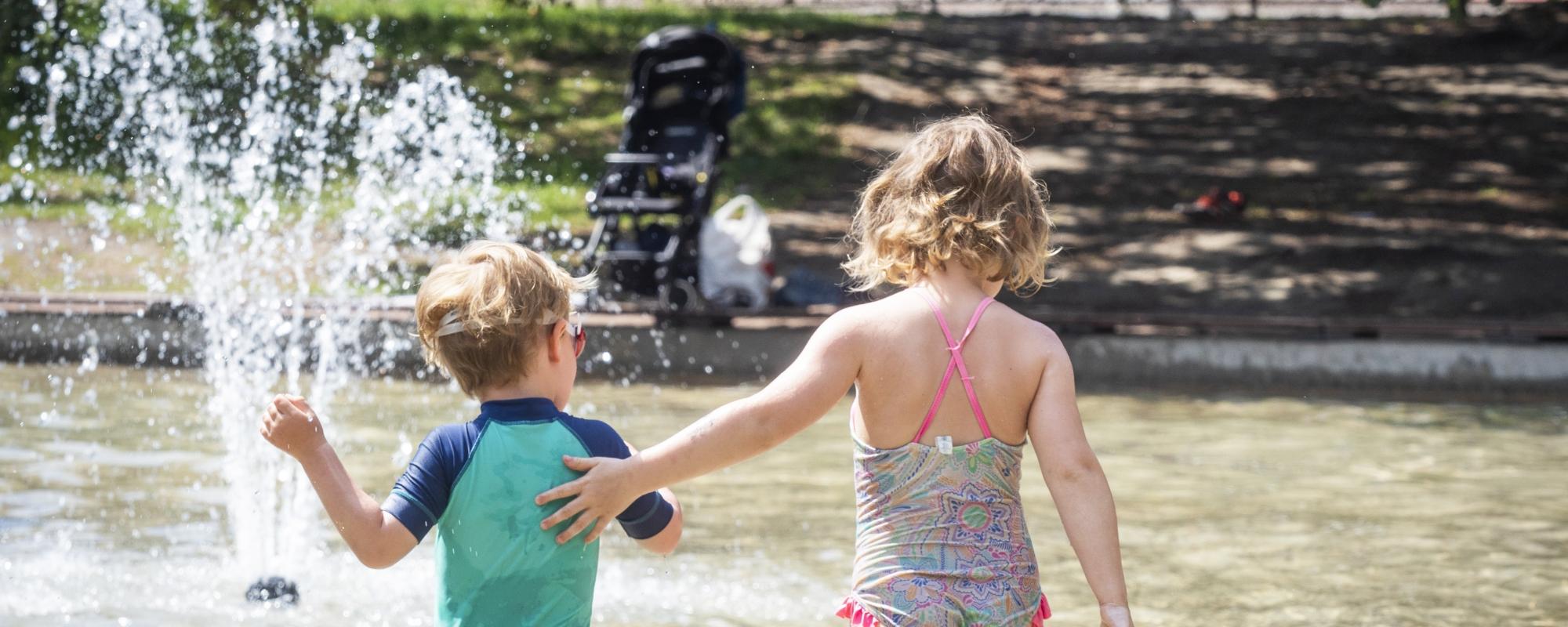 Två barn badar i plaskdammen.