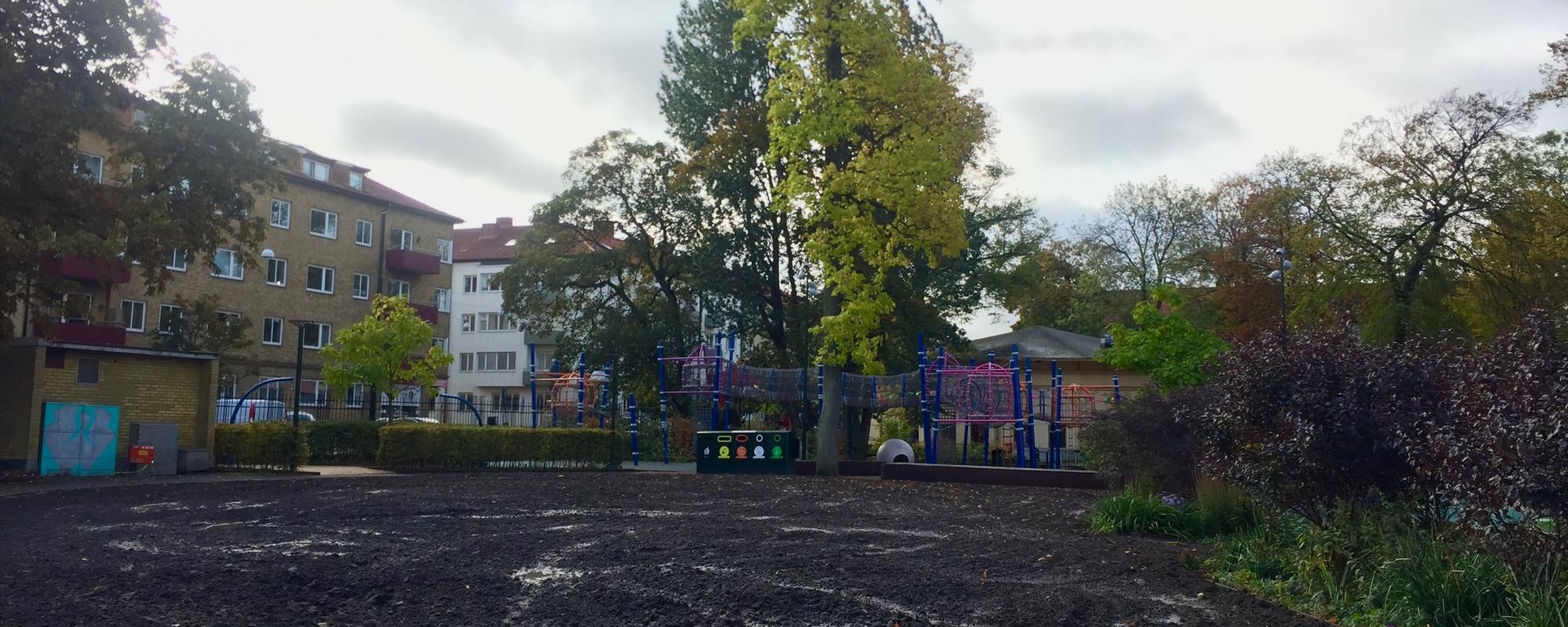 En yta som är täckt av jord. I bakgrunden skymtar en lekplats.