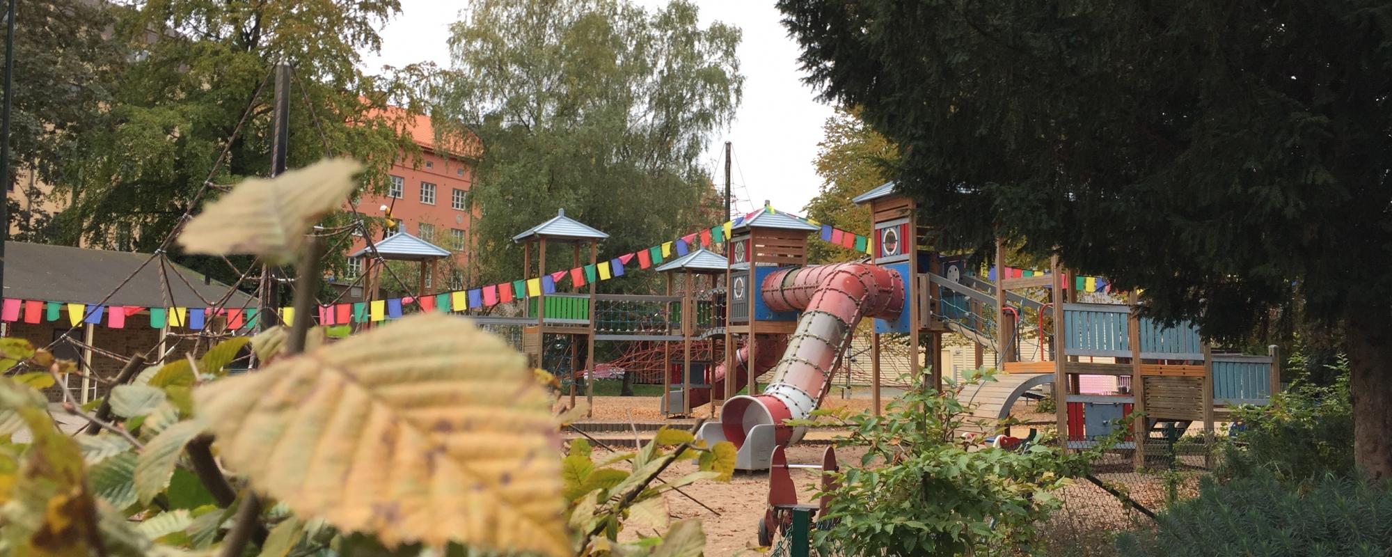 Lekplats skymtar bakom gröna buskar och träd. Färgglada flaggor synd också.