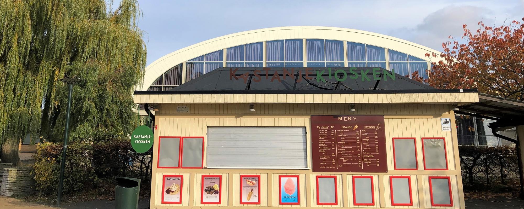 Bild på Kastanjekiosken. På kioskens framsida sitter en meny. Amiralen skymtar i bakgrunden.