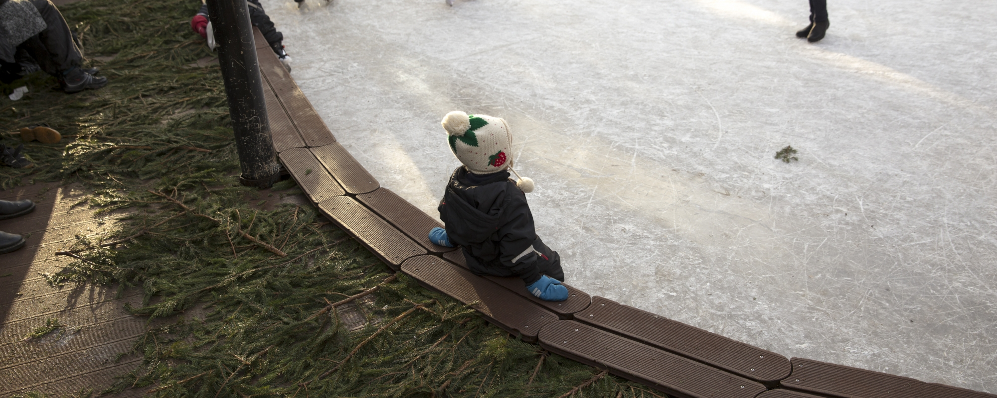 Ett barn står i kanten av en isbana. Runt isbanan ligger granris.