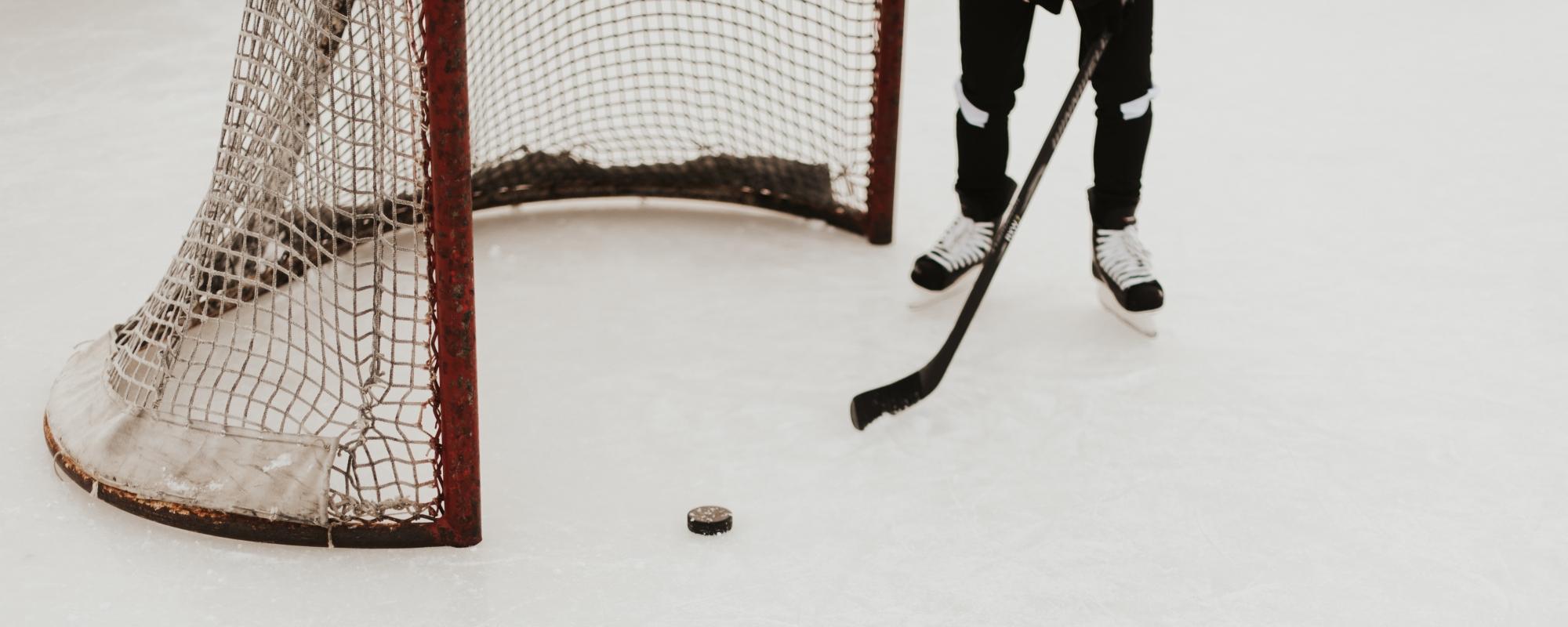 En person spelar ishockey. Står framför ett hockeymål.