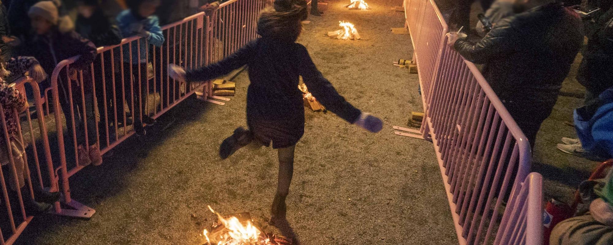 Flicka hoppar över sju små eldar