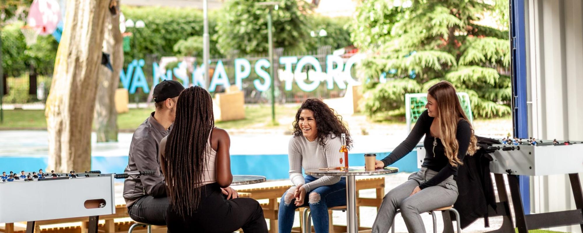 Fyra personer sitter och samtaler, en skrattar. I bakgrunden skymtar texten Vänskapstorget
