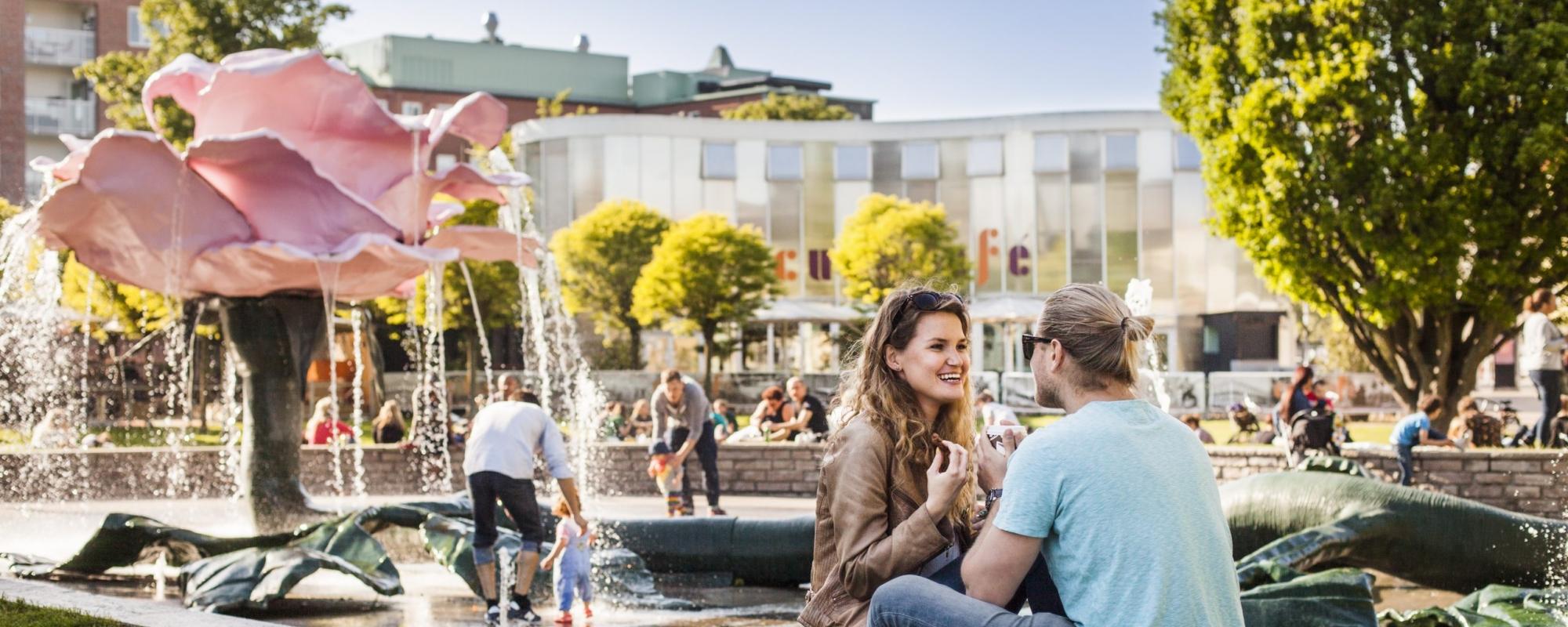 två personer sitter vid rosfontänen i bakgrunden syns orangeriet vid folkets parks huvudentré