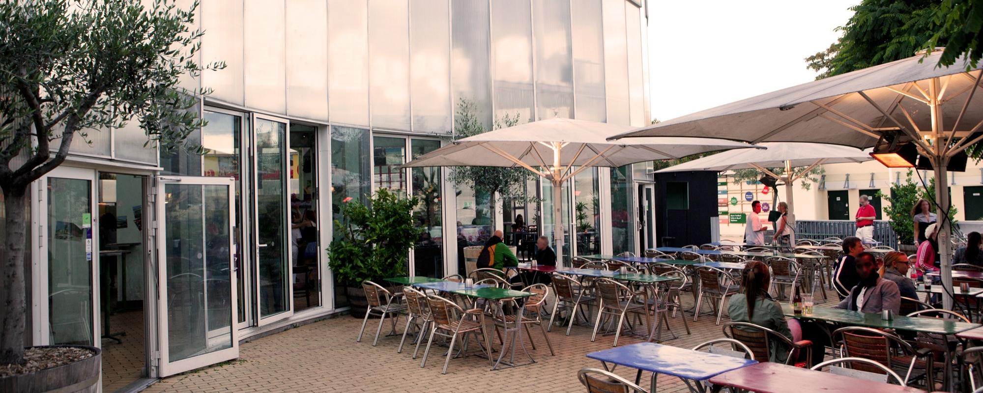 Glasbyggnaden Folkets Orangeri i dagsljus. Framför byggnaden stå några bord, stolar och parasoll.