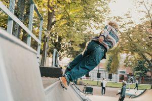 En person balanserar på en skateboard på krönet av en skateramp. Hen har ryggen mot kameran