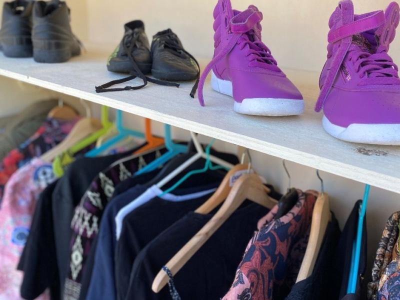 Bild på klädboden. På hyllplanen står skor och nedanför hänger kläder på galjar.