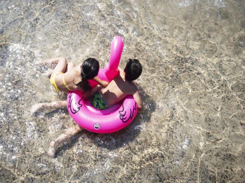 Bilden visar två barn uppifrån som leker i plaskdammen