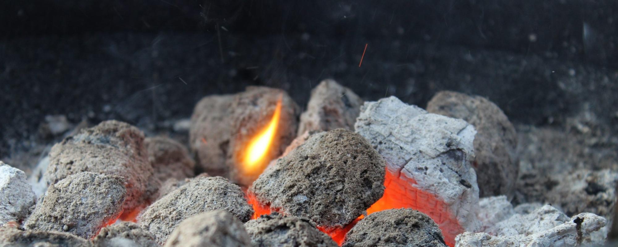 Bilden visar grillkol som glöder på ett svart fat.