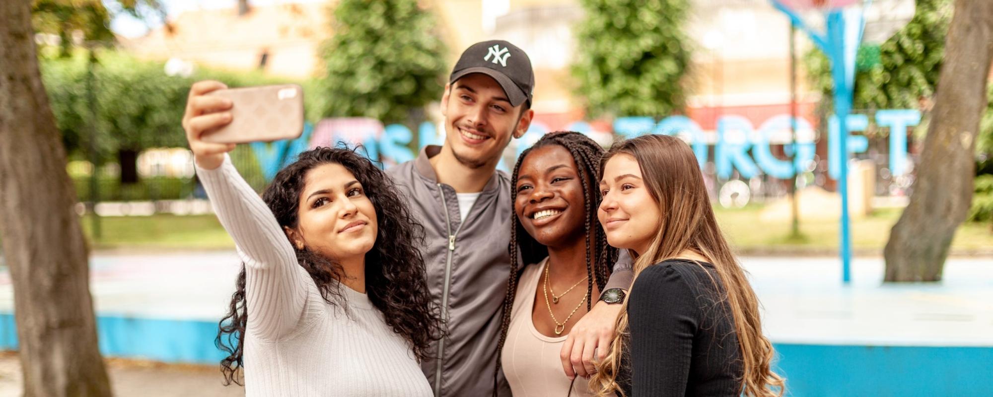 Fyra personer ler mot en mobilkamera. En av personerna håller mobilkameran med en utsträckt arm.