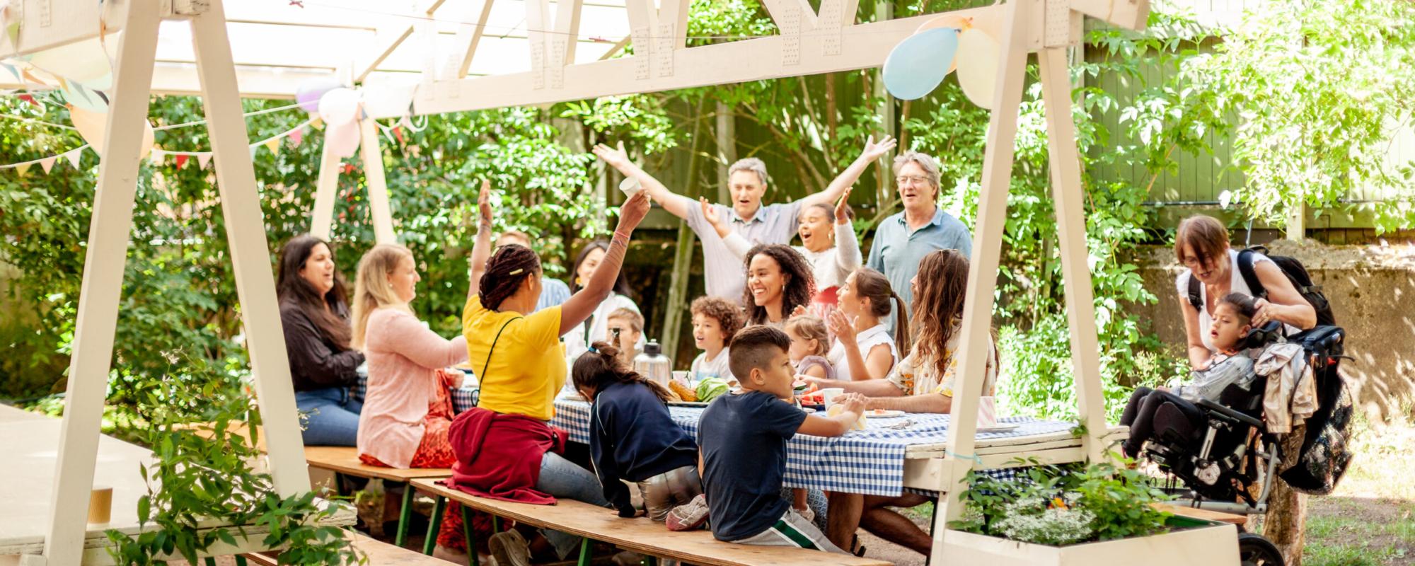 Barn och vuxa sitter vid ett picknickbord. En person håller i två ballonger.