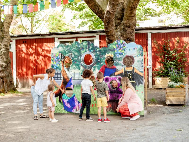 Barn och vuxna står framför en fantasifull fotovägg i Folkets Park