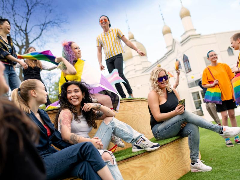 Bild på unga personer som sitter på parktorget i Folkets Park. I bakgrunden skymtas Moriska Paviljongen.